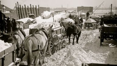 PHOTO: Carts haul snow and ice, cleared from city streets, to the river for dumping in the East River in New York, possibly during the Blizzard of 1888.
