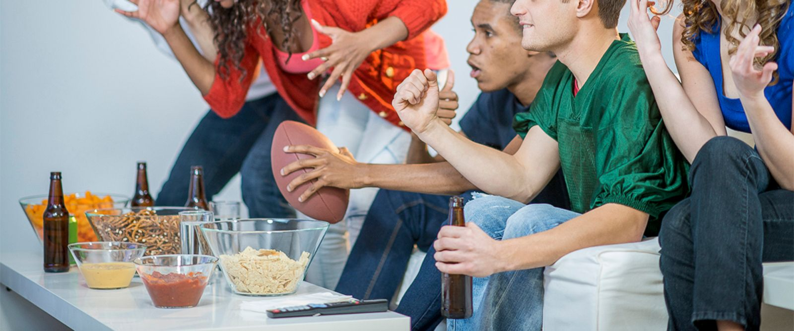 PHOTO: People cheer while watching a football game on television in an undated stock photo.