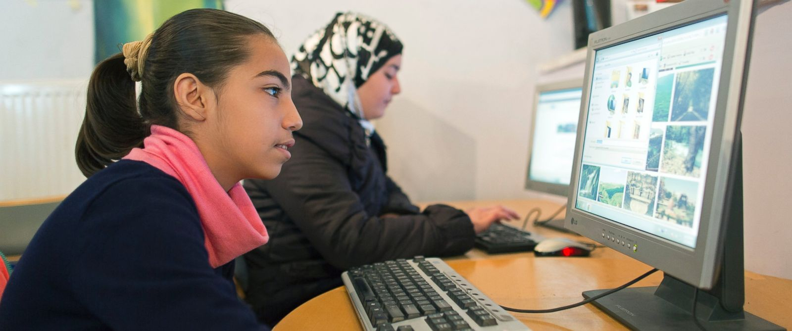PHOTO: Two girls surf the internet in the child and family protection zone for Syrian refugees in Jordan.