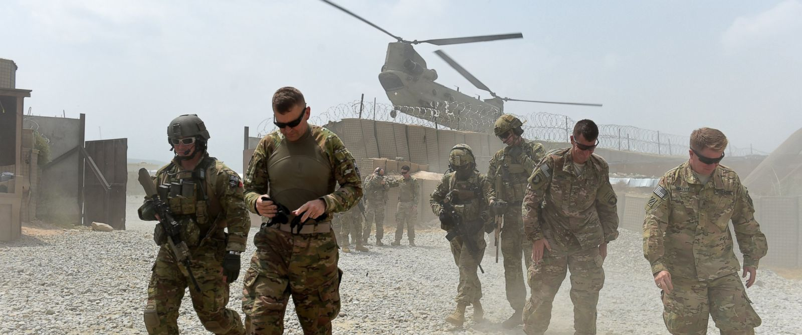 PHOTO: In this photograph taken on August 13, 2015, US army soldiers walk as a NATO helicopter flies overhead at coalition force Forward Operating Base (FOB) Connelly in the Khogyani district in the eastern province of Nangarhar.