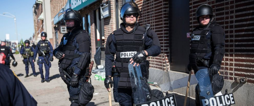 PHOTO: Police officers relax while monitoring the situation near a CVS pharmacy that was looted and burned by rioters on Monday after the funeral of Freddie Gray, April 29, 2015, in Baltimore.