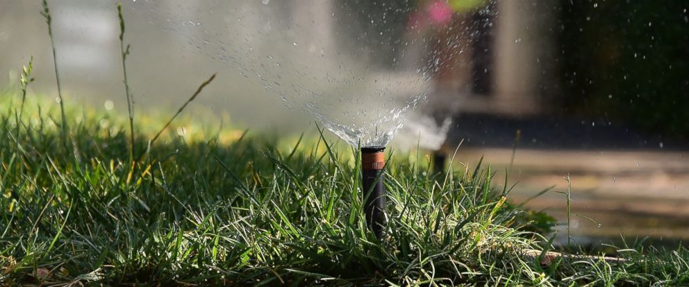 PHOTO: Sprinklers water a patch of grass on the sidewalk in front of a house in Alhambra, Calif. on July 25, 2014.