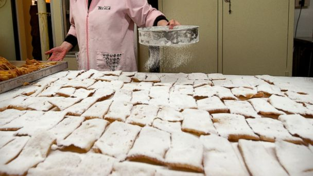 PHOTO: Giovanna Tonolo of the Pasticceria Tonolo dusts icing sugar on Galani or Chiacchiere (Carnival sweet fritters) another traditional Carnival sweet in Venice, Italy, Feb. 8, 2012.