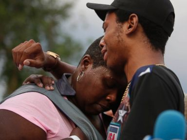 PHOTO: Activist Lamon Reccord, center, consoles Sheila Jones, center, mother of Africa Bass during a vigil for Bass, who was killed as she walked through her apartment complex July 27, 2016, in Chicago.