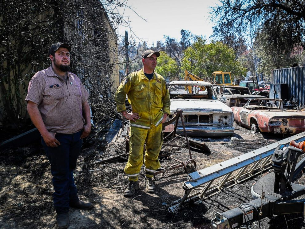 PHOTO: Residents Wade Holley, left, and Mike Boyce look over the damage to their cars in the Clayton Fire at the Clearlake machine shop in Lower Lake, California, Aug. 16, 2016.
