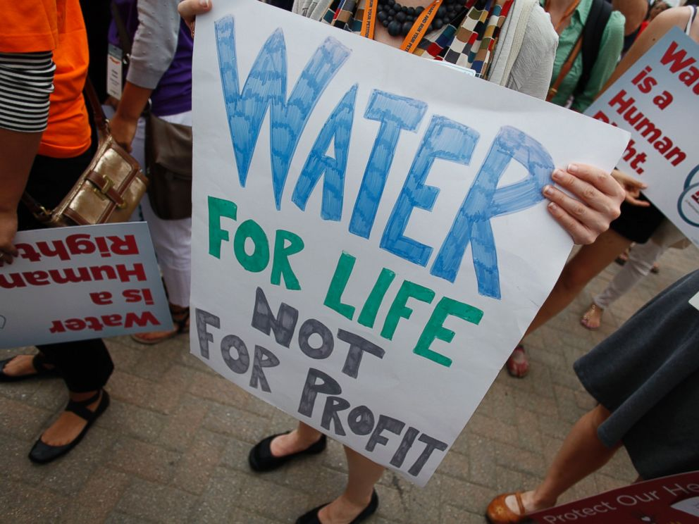 PHOTO: Demonstrators hold signs as they protest against the Detroit Water and Sewer Department July 18, 2014 in Detroit, Mich.