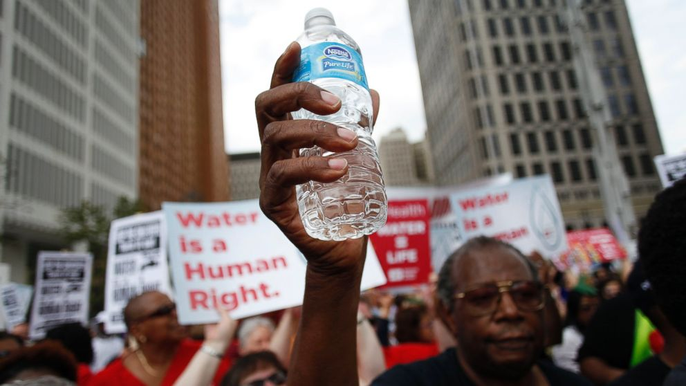 PHOTO: A man holds a bottle of water as he joins other demonstrators protesting against the Detroit Water and Sewer Department July 18, 2014 in Detroit, Mich.