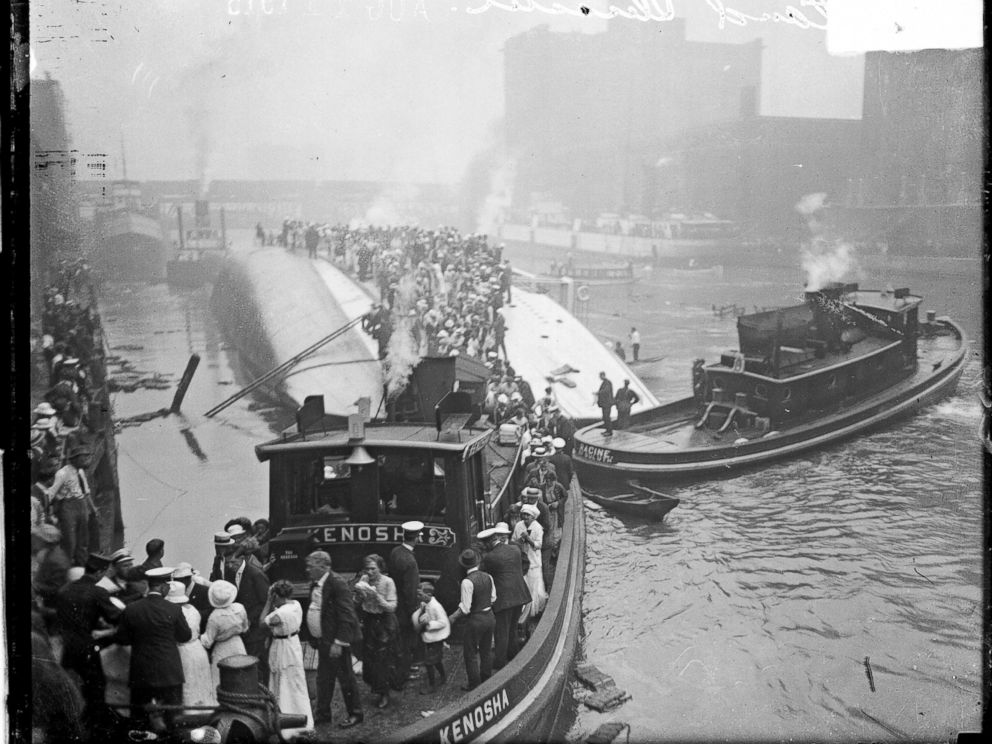 PHOTO: The Kenosha, a tugboat, rescuing survivors from the hull of the overturned Eastland steamer, Chicago, July 24, 1915.