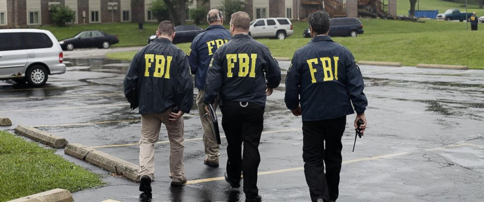 PHOTO: FBI Agents are seen in this Aug. 16, 2014 file photo investigating the shooting death of 18-year-old Michael Brown at the location where he was killed on Canfield Drive in Ferguson, Mo.
