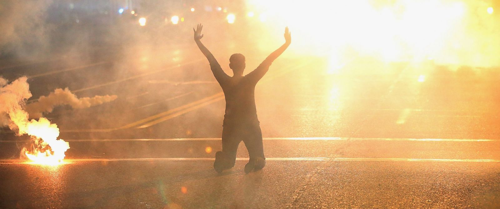 PHOTO: Tear gas surrounds a woman kneeling in the street with her hands in the air after a protest Aug. 17, 2014, in Ferguson, Mo.