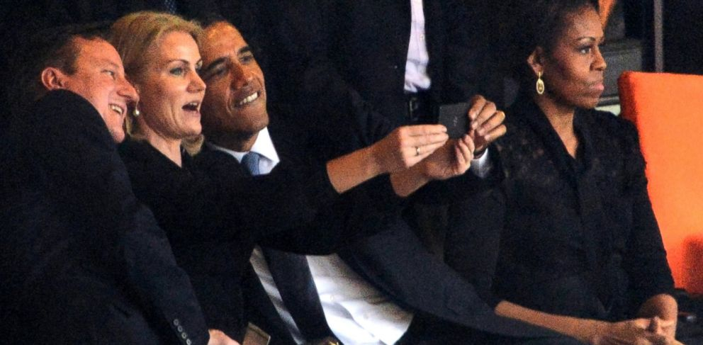 U.S. President Barack Obama (R) and British Prime Minister David Cameron pose for a selfie picture with Denmarks Prime Minister Helle Thorning Schmidt during the memorial service of South African former president Nelson Mandela, Dec. 10, 2013.