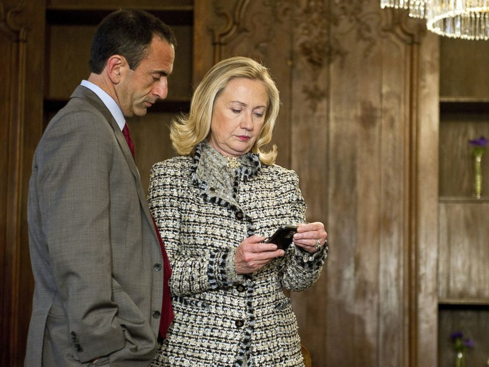 PHOTO: Hillary Clinton looks at a phone message with Assistant Secretary of State for European Affairs Philip Gordon as they wait in a conference room, Feb. 4, 2012.