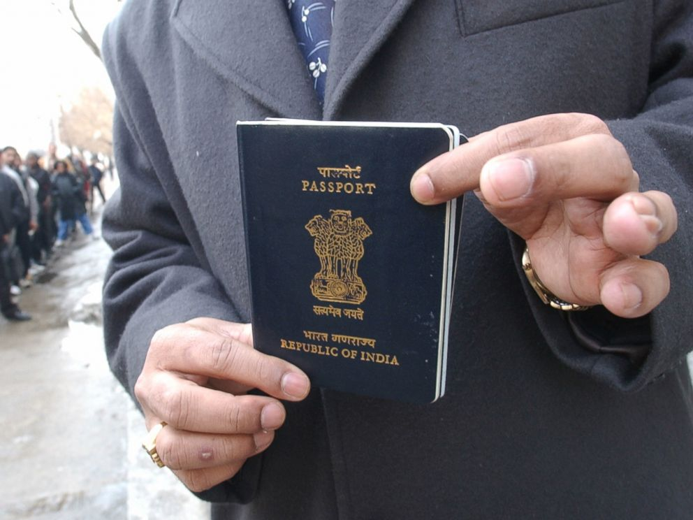 PHOTO: Yog Gorur picks up his India passport from the US CONSULATE in Toronto while other people lineup in front of U.S. CONSULATE to apply or pick up visa applications.