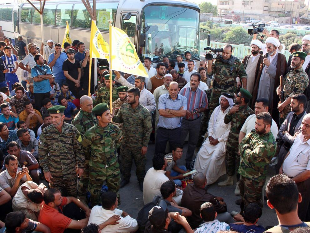 PHOTO: Iraqi civilians volunteering to fight a militant offensive gather themselves together among members of security forces on June 15, 2014, in the southern port city of Basra before going to Iraqi second city Mosul.