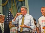 PHOTO: George Shea, left, the official announcer for the Nathans Hot Dog Eating Contest watches New York Citys Mayor Bill De Blasio eating a famous Nathans hot dog next to Joey Jaws Chestnut, right, at City Hall on July 3, 2014 in New York City.