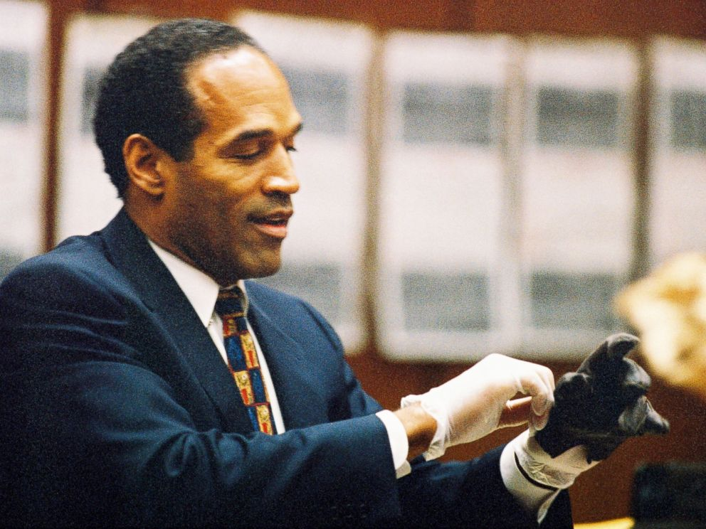 PHOTO: O.J. Simpson tries on a leather glove allegedly used in the murders of Nicole Brown Simpson and Ronald Goldman during testimony in Simpsons murder trial, June 15, 1995, in Los Angeles.