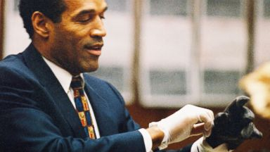 PHOTO: O.J. Simpson tries on a leather glove allegedly used in the murders of Nicole Brown Simpson and Ronald Goldman during testimony in Simpsons murder trial June 15, 1995 in Los Angeles.