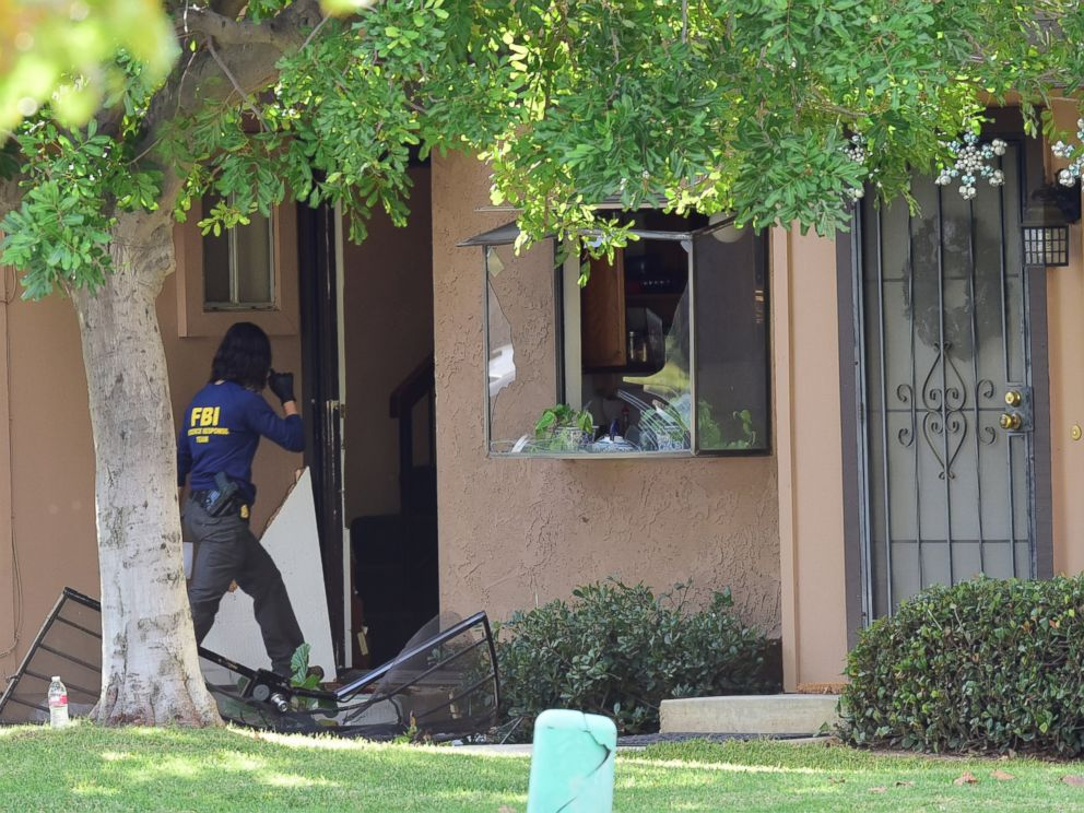 PHOTO: An member of an FBI evidence response team walks over a destroyed door to enter a townhome in Redlands, Calif., Dec. 3, 2015, linked to the Dec. 2 shooting rampage in San Bernardino.