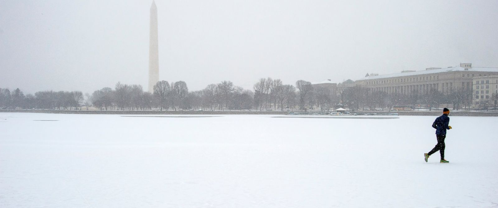PHOTO: A jogger runs past the frozen Tidal Basin as a light snow falls on Presidents Day, Feb. 16, 2015 in Washington.