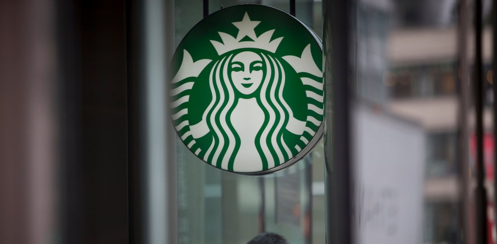 PHOTO: Pedestrians pass in front of a Starbucks Corp. location in New York, U.S., on Tuesday, April 23, 2013.