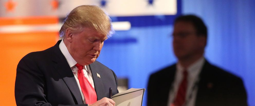 PHOTO: Republican presidential candidate Donald Trump signs a book during a commercial break in the Fox Business Network Republican presidential debate at the North Charleston Coliseum and Performing Arts Center, Jan. 14, 2016, in North Charleston, S.C.