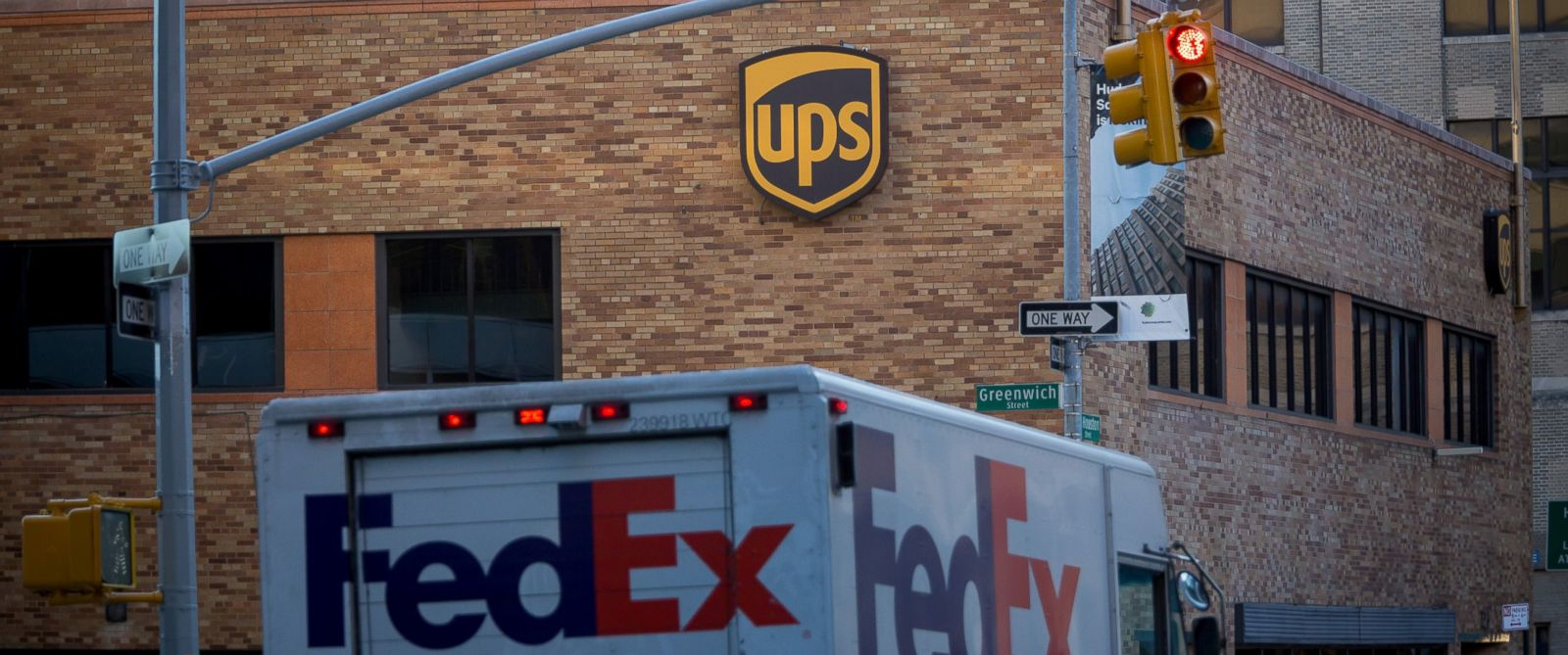PHOTO: A FedEx Corp. truck passes a United Parcel Service Inc. facility in New York, Oct. 23, 2015.