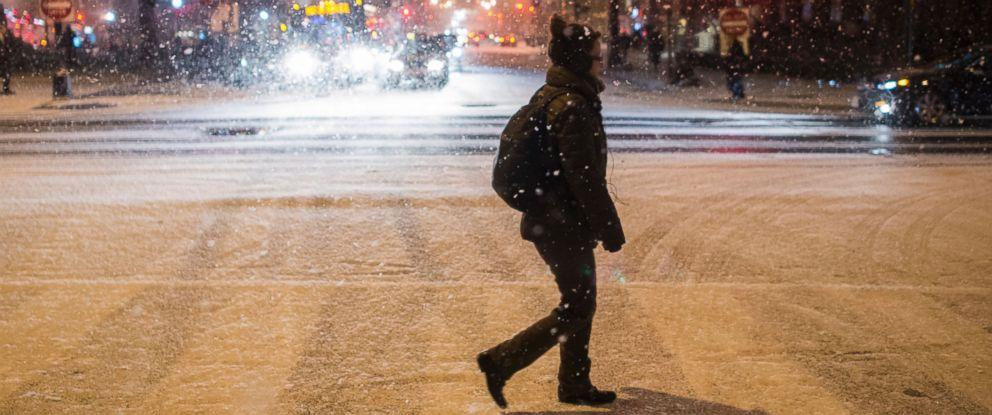 PHOTO:A woman crosses the street as it snows in Washington, Jan.20, 2016.