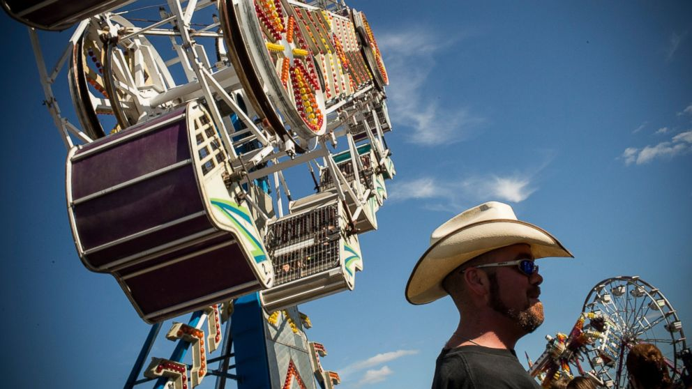 PHOTO: A man stands beneath a ride at the North Dakota state fair, July 27, 2013, in Williston, North Dakota.