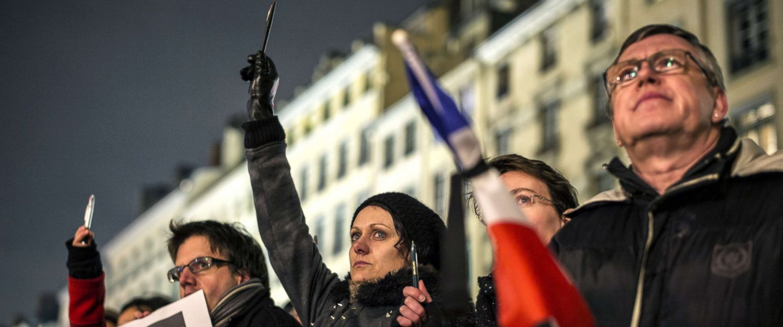 PHOTO:A woman cries as she holds up a pen during a vigil in Lyon on January 7, 2015, following an attack by gunmen on the offices of the satirical weekly, Charlie Hebdo in the capital.