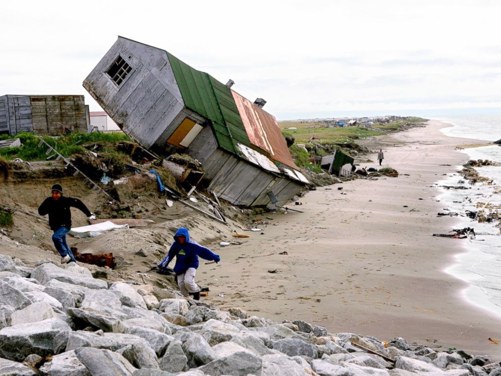 Photo a home destroyed by beach erosion tips over in the the alaskan