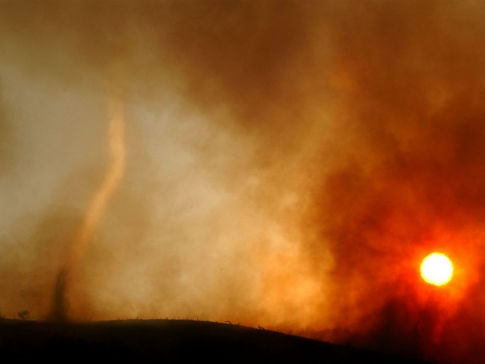 PHOTO: A wildfire-induced tornado of hot ash dances across a ridgetop as the sun sets May 13, 2002 near Rancho Santa Margarita, CA.