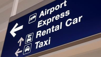 PHOTO: An airport sign with direction arrows for rental cars and taxis.