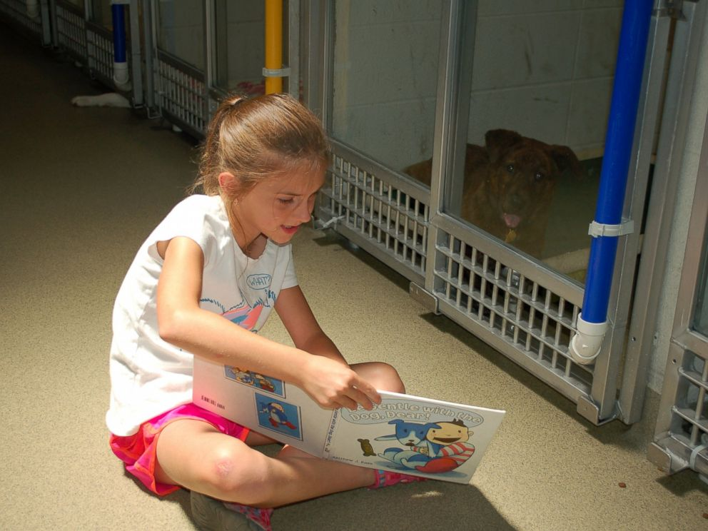 PHOTO: Caitlyn Huntebrinker reads holiday stories to a Humane Society of Missouri shelter dog during the Deck the Howls event for the Shelter Buddies Reading Program.