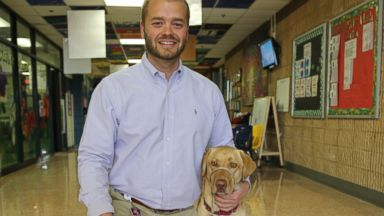 PHOTO: U.S. Army Specialist and school teacher Dustin Deweerd with Gunny his service dog at Duncanville Elementary School.