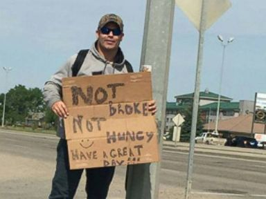 "PHOTO: A plainclothes police officer with the Regina Police Service in Saskatchewan holds a sign that says ""I'm not broke. Im not hungry. Have a great day! as part of a project to observe driver behavior."