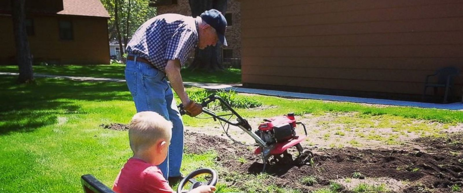 PHOTO: Erling, left, and Emmett tilling the garden together.