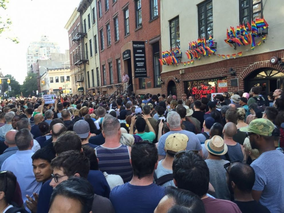 PHOTO: People gather outside the Stonewall Inn in New York City to pay tribute to the victims of a mass shooting at a gay club in Orlando, June 12, 2016.