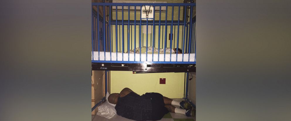 PHOTO: Amy Palmer photographed a heartwarming photo of her husband sleeping under the crib of her son who was staying at the hospital.
