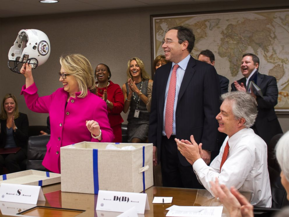 PHOTO: Hillary Clinton receives a football helmet in a State Department meeting from Deputy Secretary Tom Nides, Jan. 7, 2012.