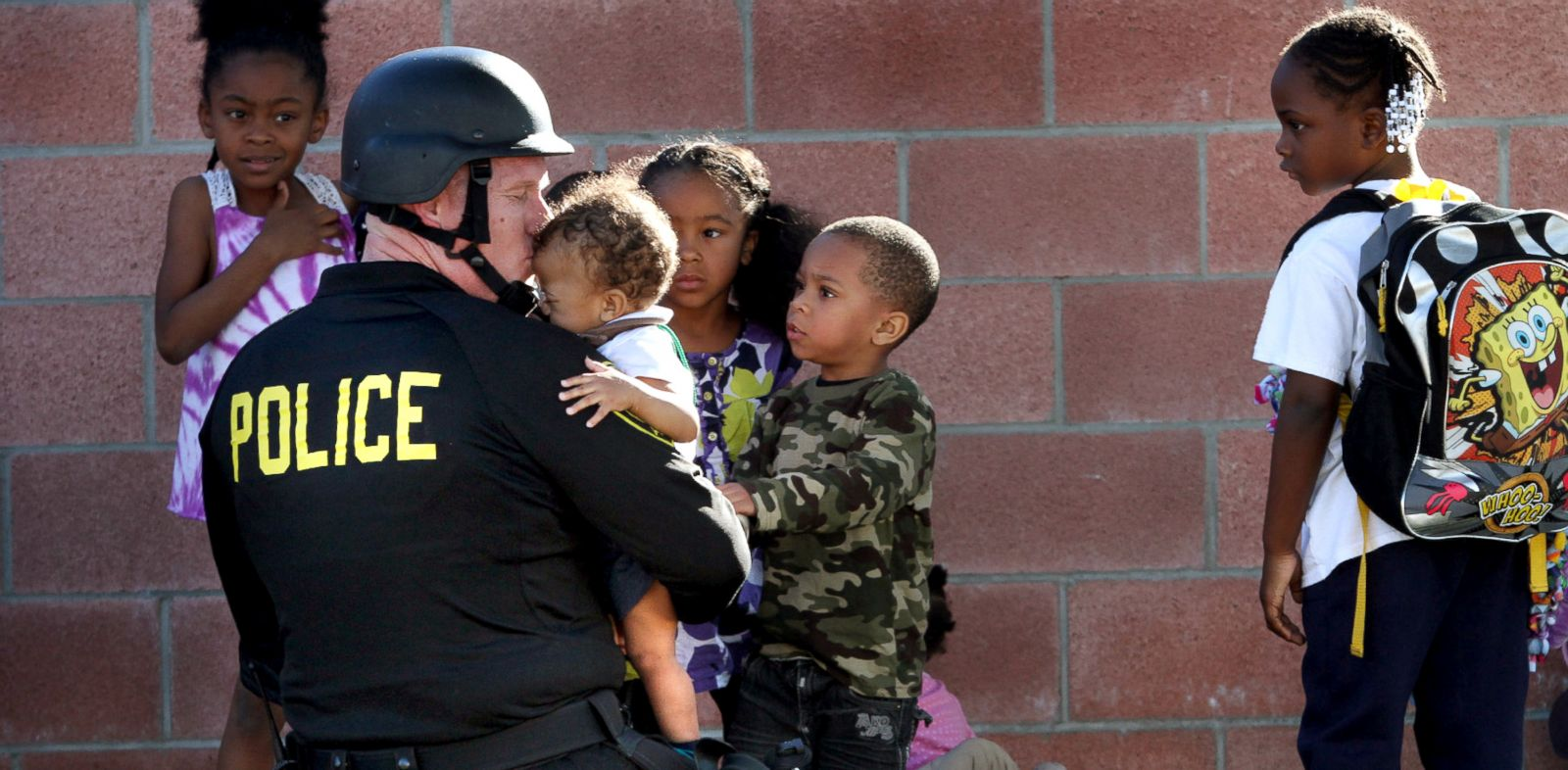 PHOTO: Inglewood police officer Joey Zeller kisses the head of toddler he led to safety with a group of others from the neighborhood where two police officers were shot in what began as a domestic dispute that led to a hostage situation, Nov. 27, 2013.