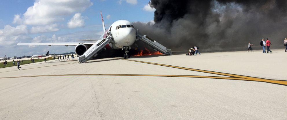 PHOTO: Passengers flee a burning Dynamic Airlines plane at Fort Lauderdale International Airport.