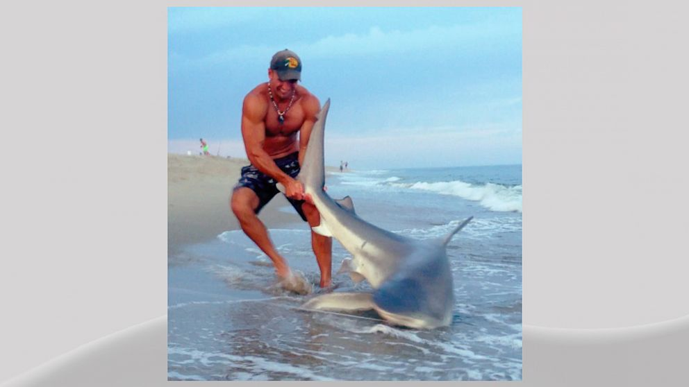 PHOTO:  Elliot Sudal is seen in this image wrestling a 7-foot-long shark to shore.