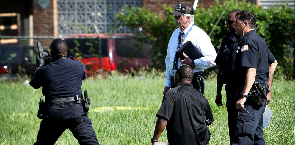 PHOTO: Memphis police officers and investigators recover a hand gun from a field on the 4600 block of Cottonwood near the scene where officer Sean Bolton was shot and killed during a traffic stop in Parkway Village, Memphis, Tenn., Aug. 2, 2015.