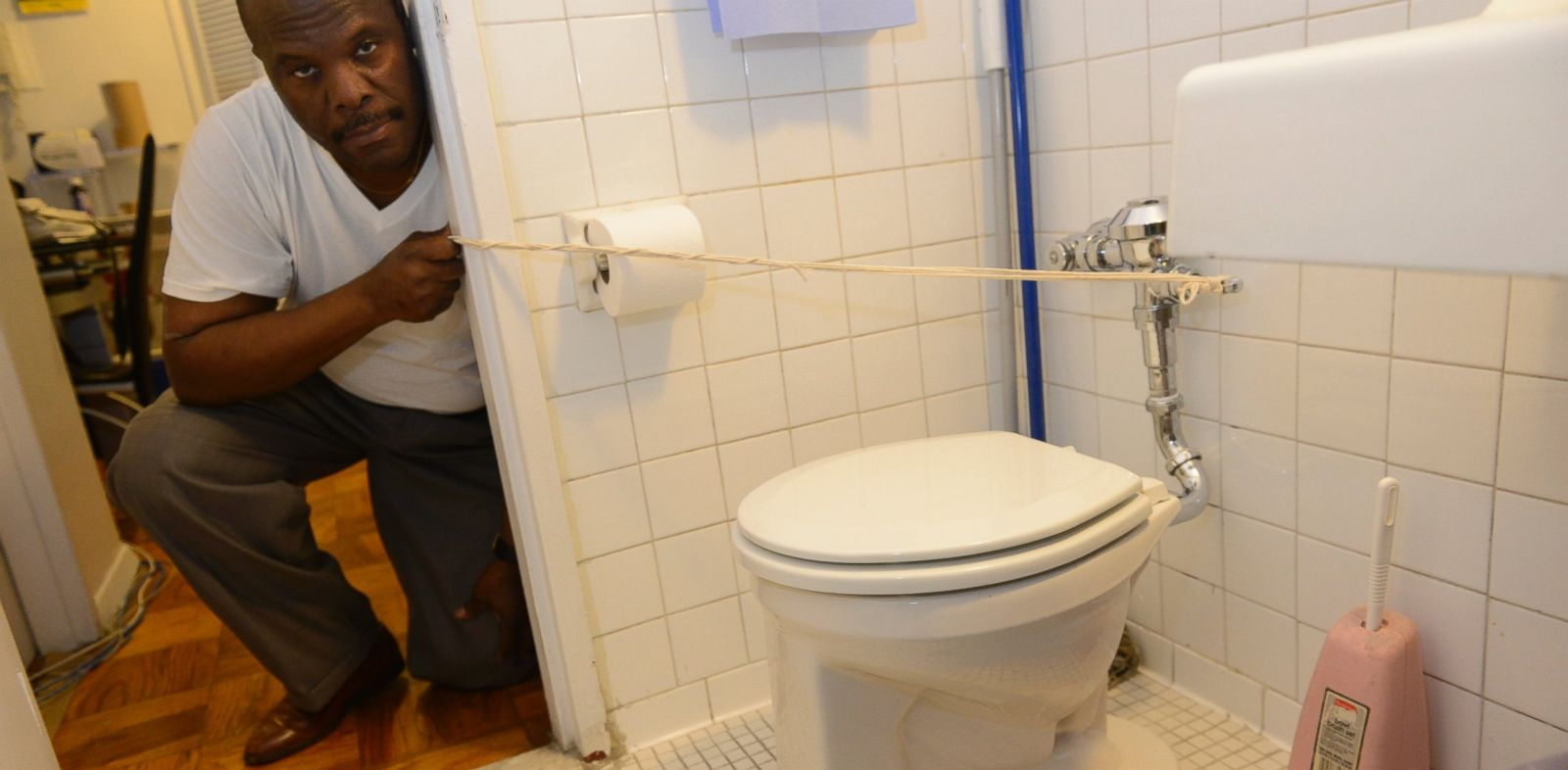 PHOTO: Michel Pierre, pictured using a rope to flush his repaired toilet, Oct. 9, 2013.
