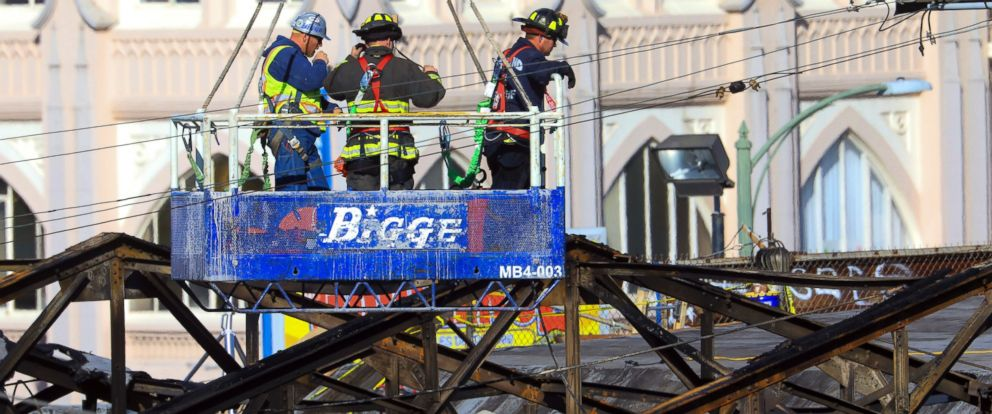 PHOTO: Firefighters and a worker are lifted by a crane into a warehouse that burned in Oakland, California, Dec. 6, 2016.