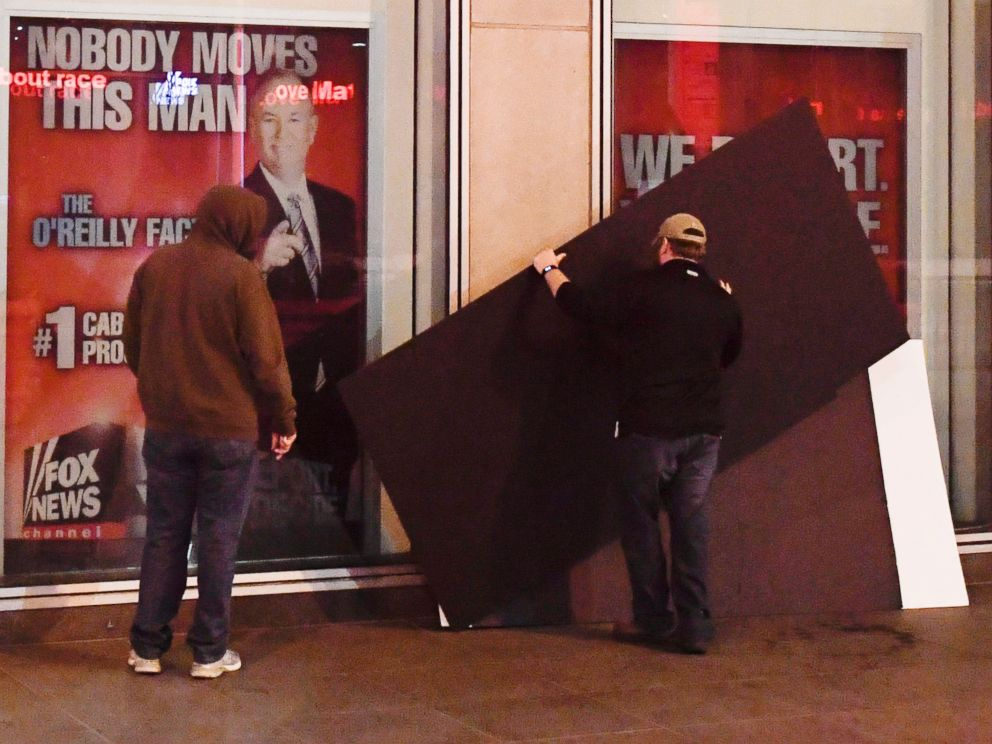 PHOTO: Men place boards over a poster of former cable news host Bill OReilly outside of the Fox News offices in Manhattan, April 20, 2017.