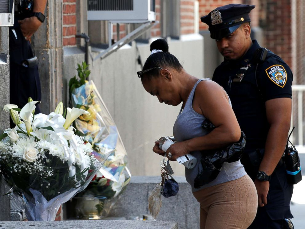 PHOTO: Local resident Maria Ramos places a candle at a makeshift memorial outside the New York City Police Departments 46th precinct after a gunman fatally shot a female officer in an unprovoked attack in the Bronx, New York, on July 5, 2017.