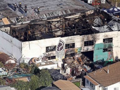 PHOTO: Recovery teams examine the charred remains of the two-story converted warehouse that caught fire killing dozens in Oakland, California, Dec. 4, 2016.