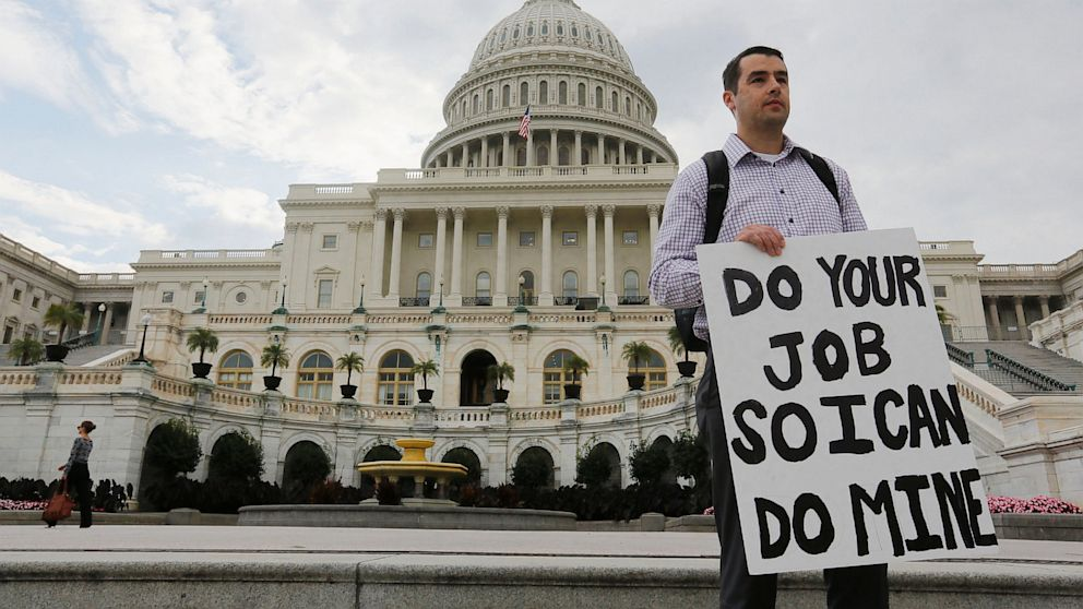 PHOTO: A furloughed federal employee holds a sign on the steps to the U.S. Capitol after the U.S. Government shut down last night, on Capitol Hill in Washington on October 1, 2013.