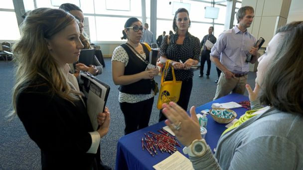 PHOTO: A job seeker listens to a recruiter at a health care job fair sponsored by the Colorado Hospital Association, May 9, 2016, in Denver.